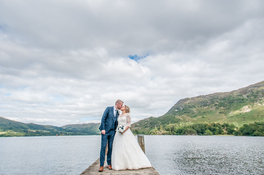 Bride and groom kiss on jetty Inn on the Lake weddings Lake District photographers