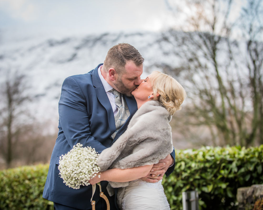 Bride and groom kissing with snowy fells, Lodore Falls, Lake District female wedding photography
