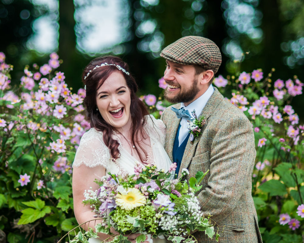 Bride and groom laughing in flowers, natural wedding photography Lake District