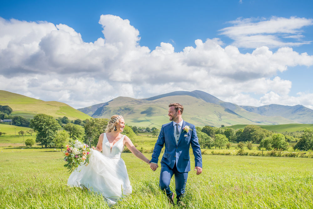 Bride and groom walking through field with Skiddaw in background Overwater Hall Lake District wedding photographers