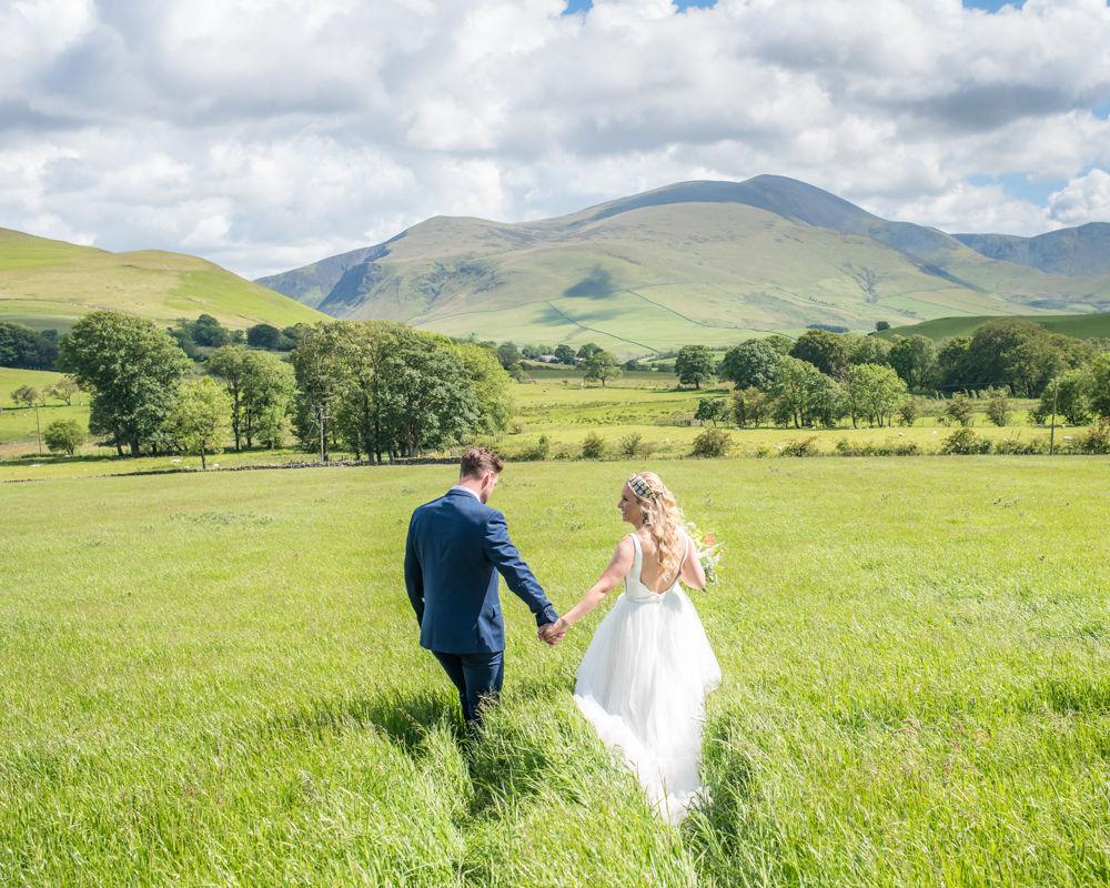 Camilla and Damian walking through fields, Lake District wedding photographers