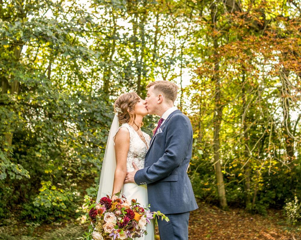 Carol Matt kiss under Autumn trees Whitley Hall Sheffield wedding photography