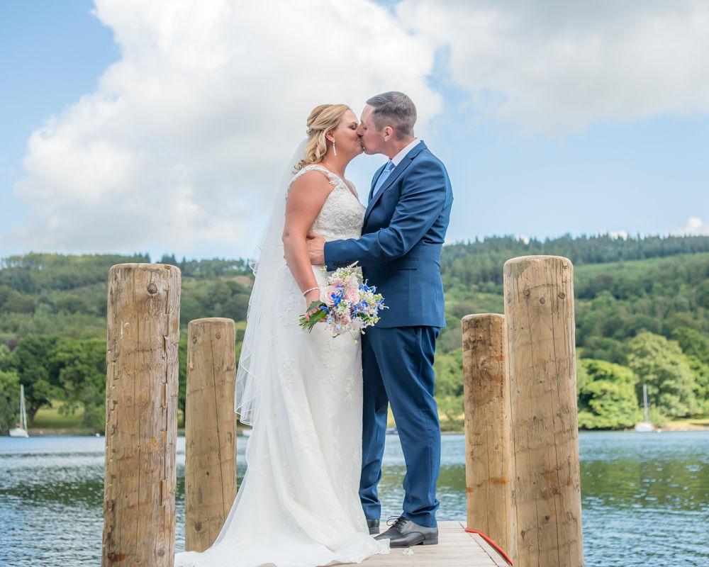 Couple kiss on jetty at Lakeside Hotel, Windermere weddings, Lake District wedding photographers