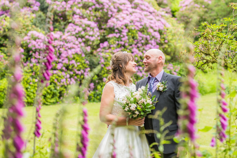 Couple looking at each other in foxgloves, Merewood House, Windermere wedding photographers Lake District