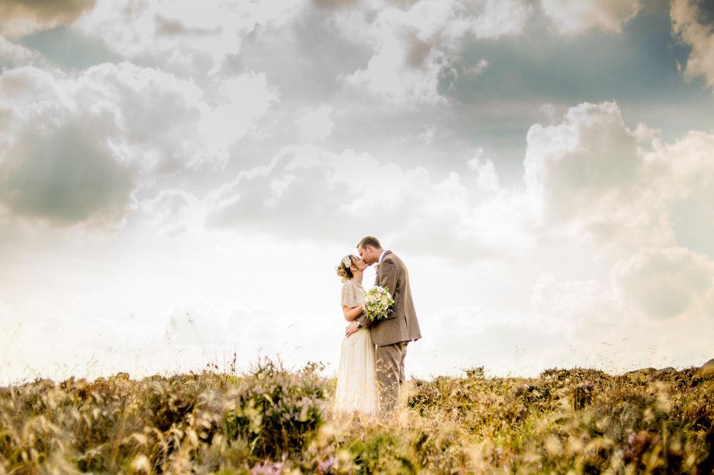 Hope & Ben kissing in wild field, Curbar Edge, Peak District wedding photographers Sheffield