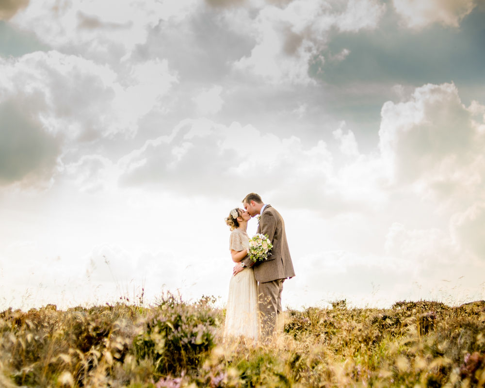 Hope and Ben kissing in flower fields, elopement wedding, Lake District wedding photographers