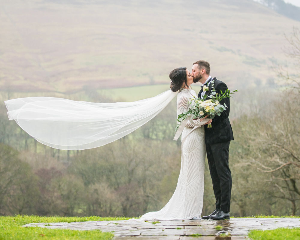 Rose and Carl kiss in rain veil blowing,Losehill House Hotel Sheffield wedding photographers.