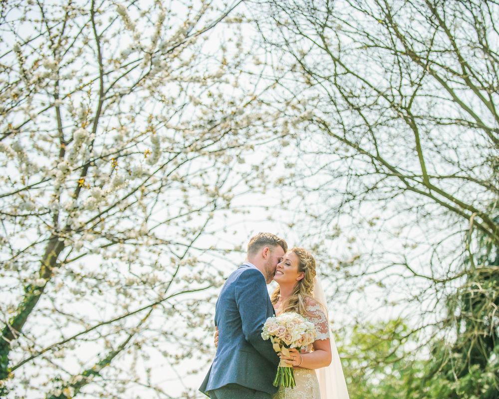 Tess Ben under blossom trees Mosborough Hall Sheffield wedding photographers