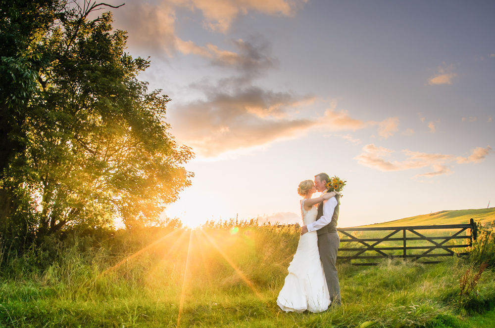 Verity and Adam kissing in field with sunset, Smallshaw Farm Cottages weddings, Sheffield wedding photography