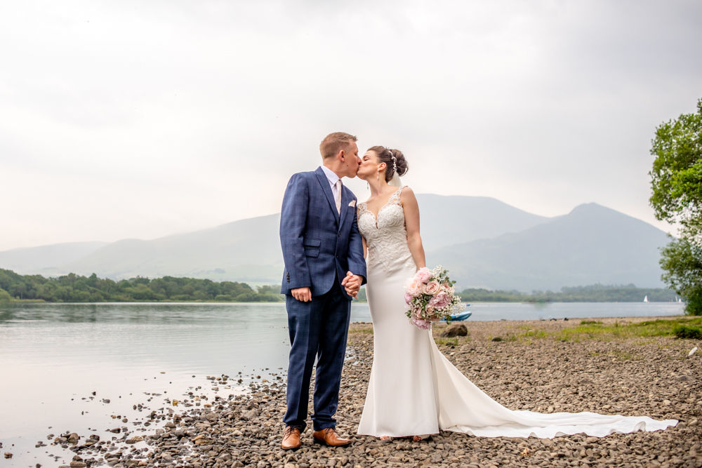 Happy couple kissing on shores of Bassenthwaite Lake, Lake District weddings elopement