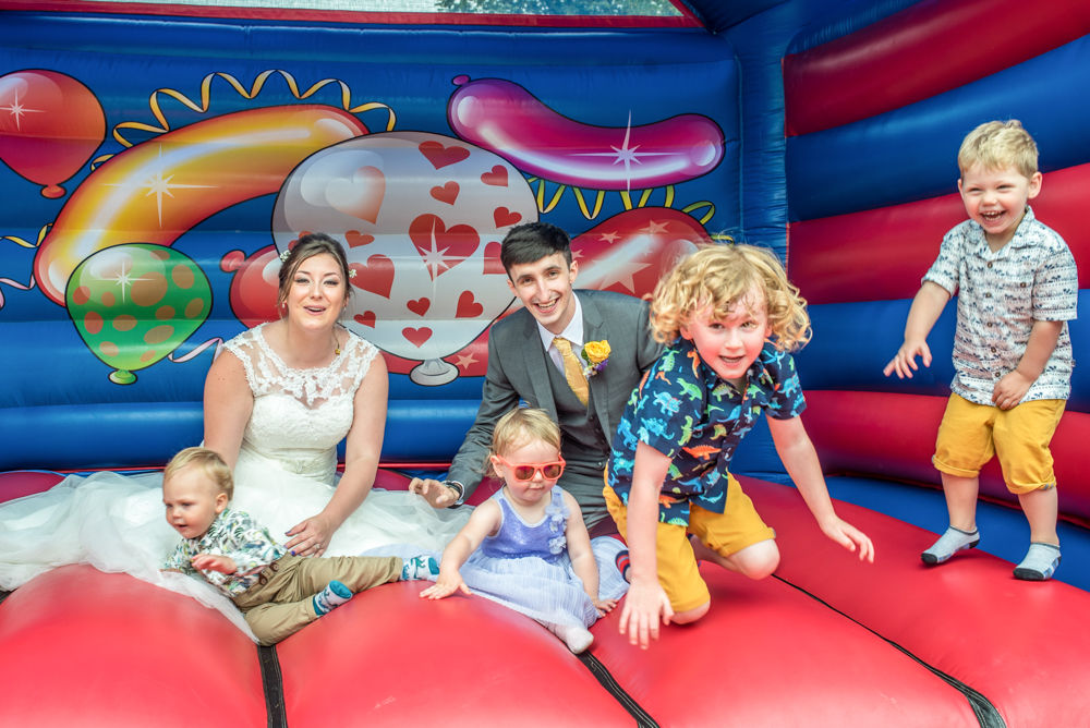 Bride and groom with neice and nephews on bouncy castle