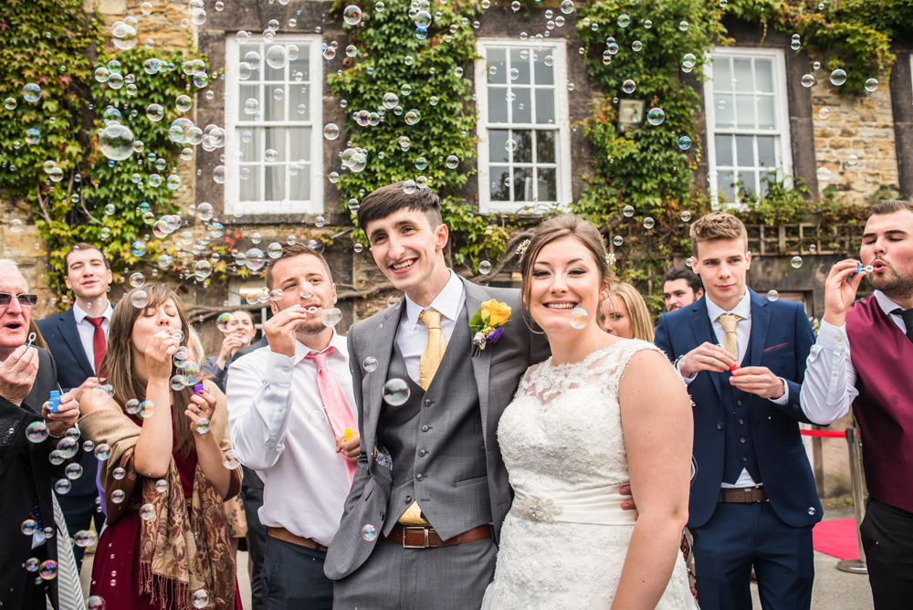 Bride and groom surrounded by friends blowing bubbles, Sheffield wedding