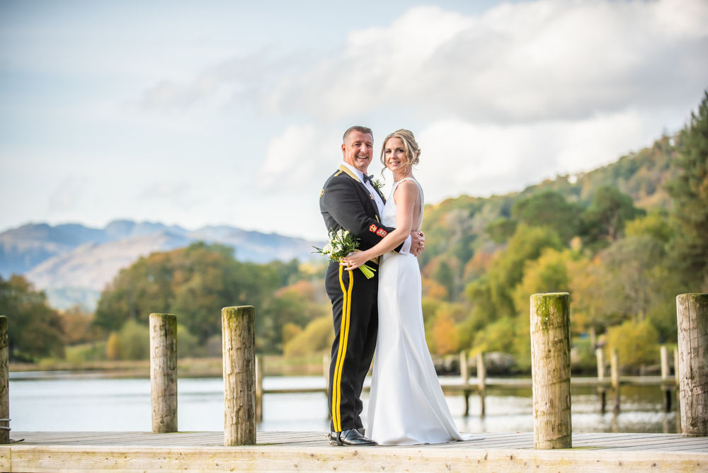 Bride and groom posing on jetty at Windermere