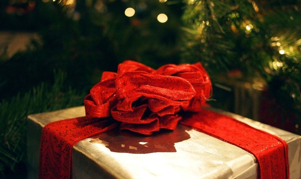 Holiday Gift wrapped with a red bow; Tips for pitching for holiday gift guides