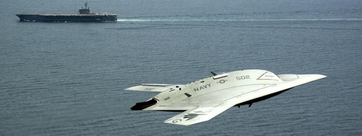An X-47B Unmanned Combat Air System flies near the aircraft carrier USS George H W Bush. Courtesy of US Navy/Wikimedia.
