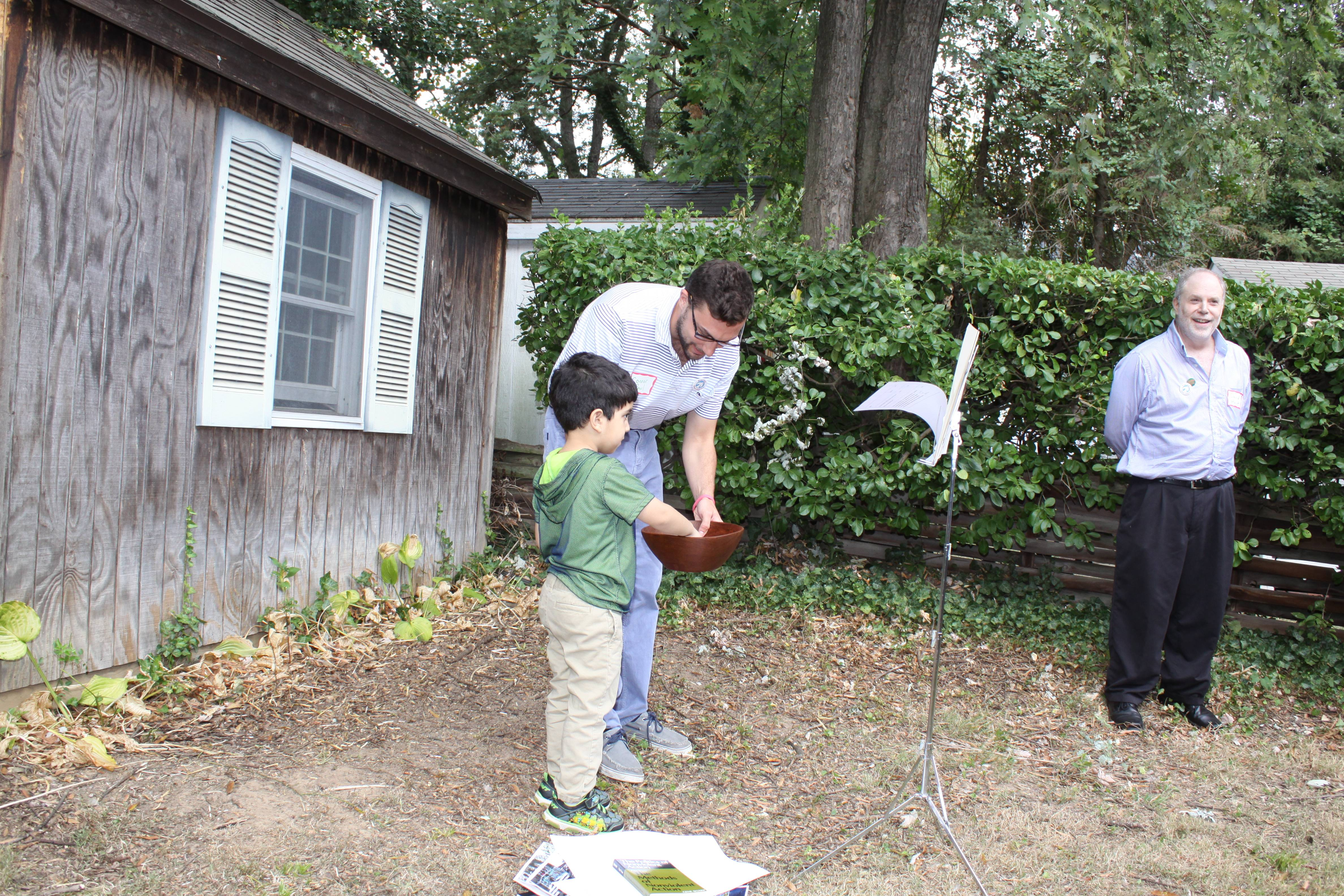 Nonviolence International intern, Connor Paul helps a young boy pick and read out raffle ticket numbers.