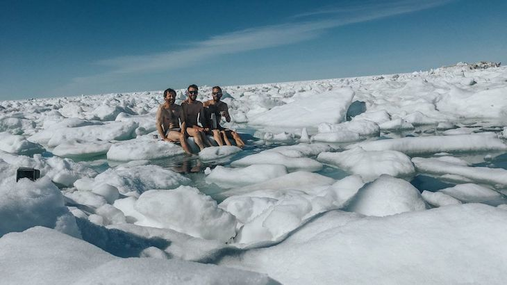 group of people sit on melting ice