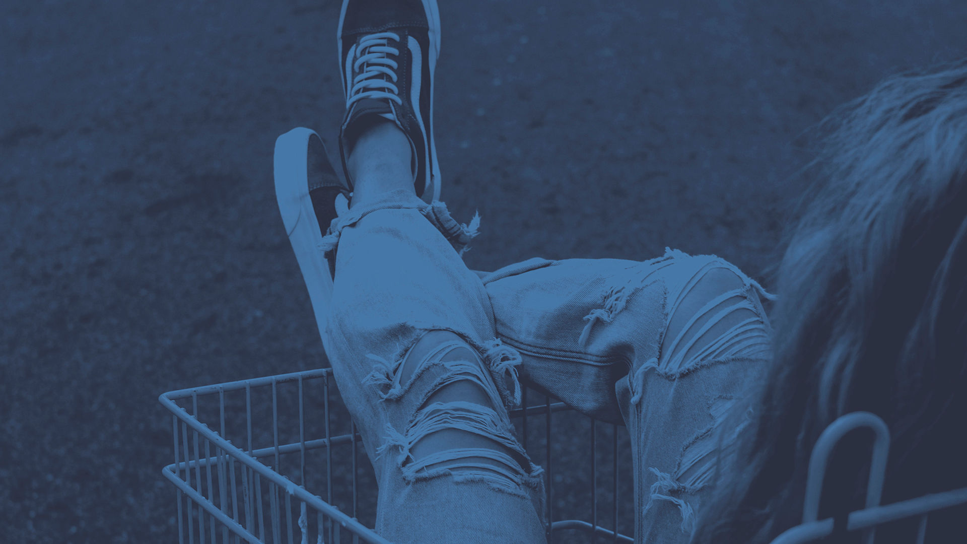 A young person sitting in a shopping trolley, wearing Vans shoes and very ripped denim jeans