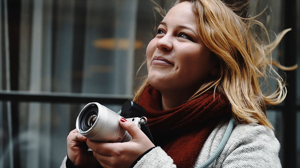 A person with long and blonde hair, wearing a light coloured coat and red scarf, preparing to take a photograph of something in the distance