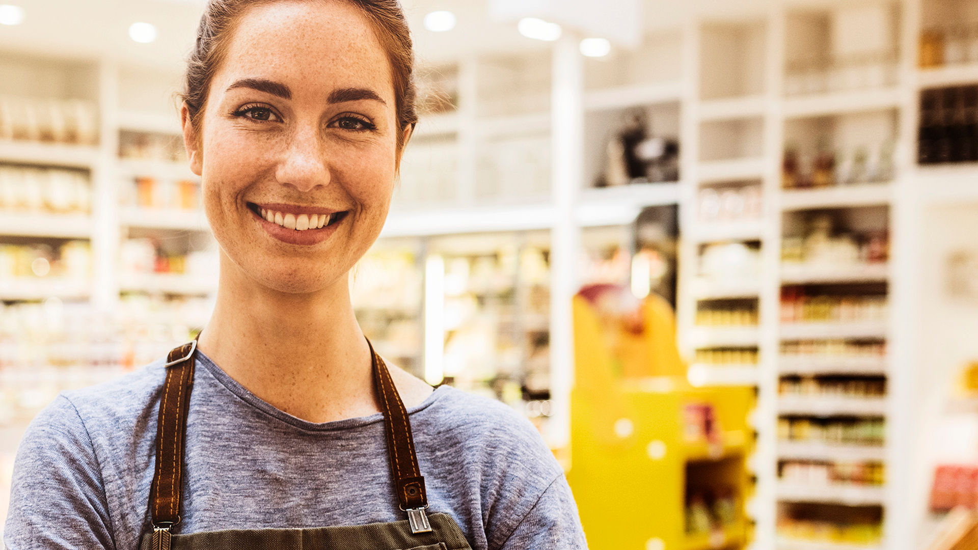 A smiling shop worker wearing a grey shirt and brown apron
