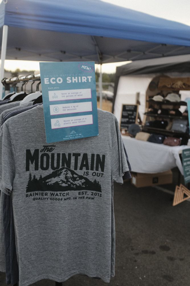 Eco friendly poster on a rack of shirts outside a pop up booth tent.