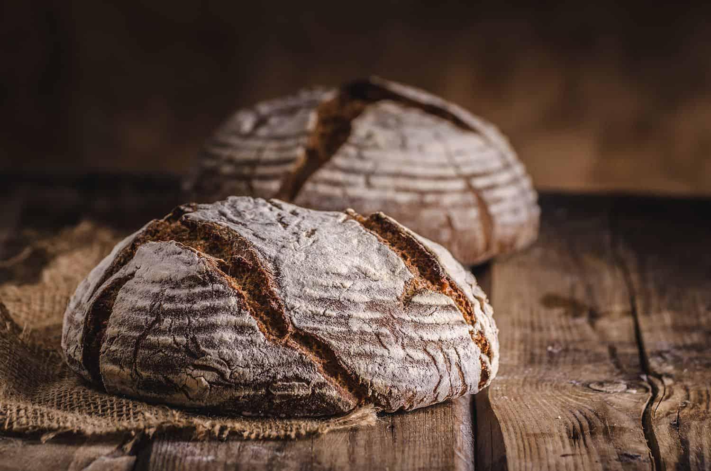 Dva sveže pečenega hlebca rženega kruha na kmečki mizi