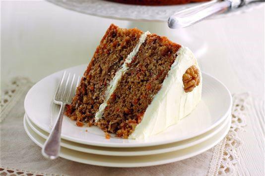 Rezina korenčkovo orehove torte z prelivom iz kremnega sira na krožničku.