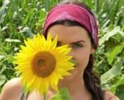 Mlada razcvetena sončnca z mladim dekletom na polju