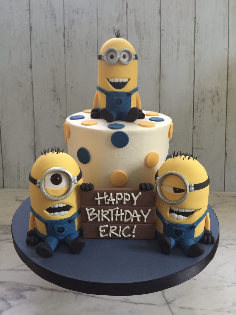 Three minions on and around a cake with polka dots