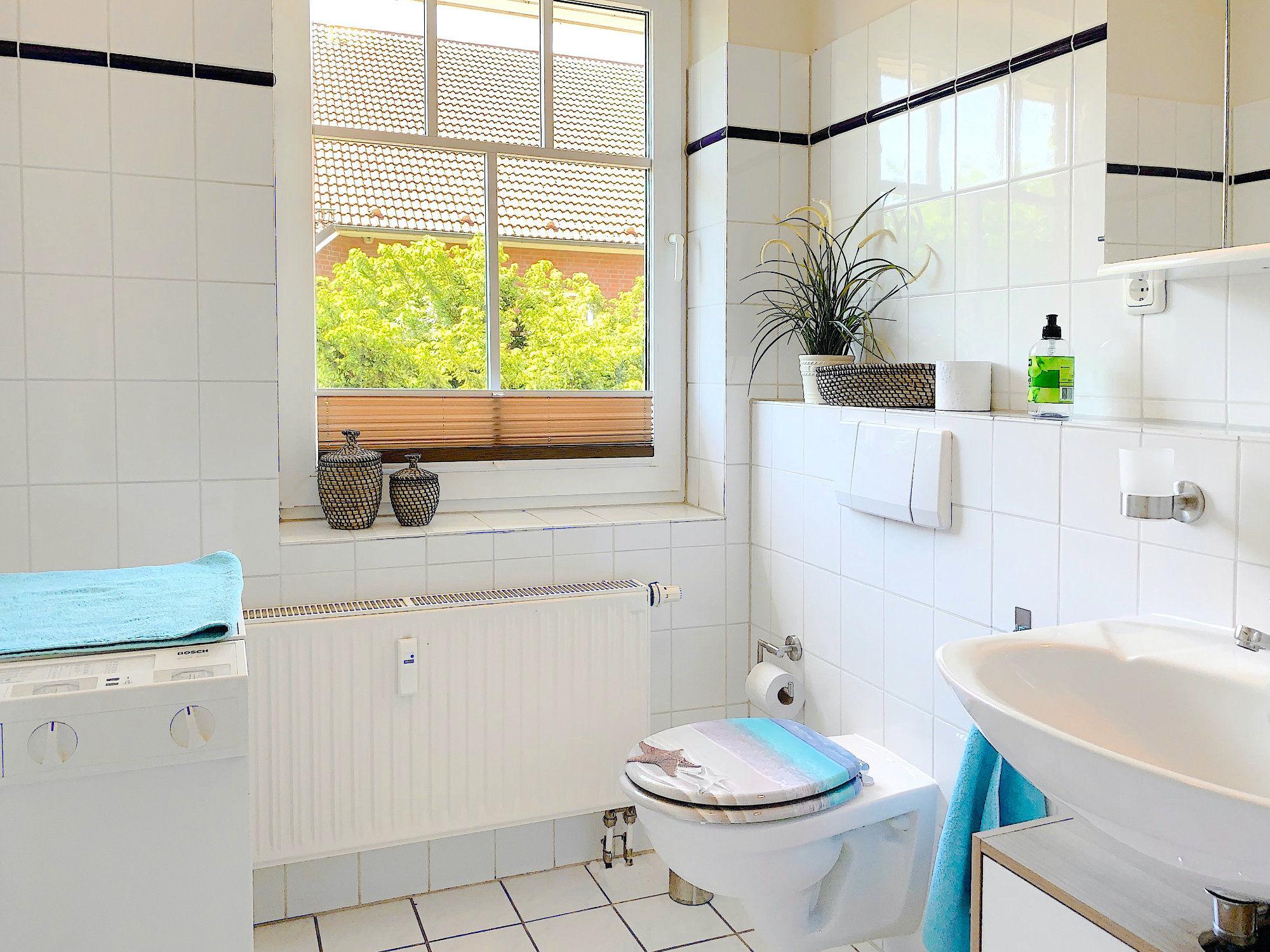 Bad mit Waschbecken, Waschmaschine und Fenster