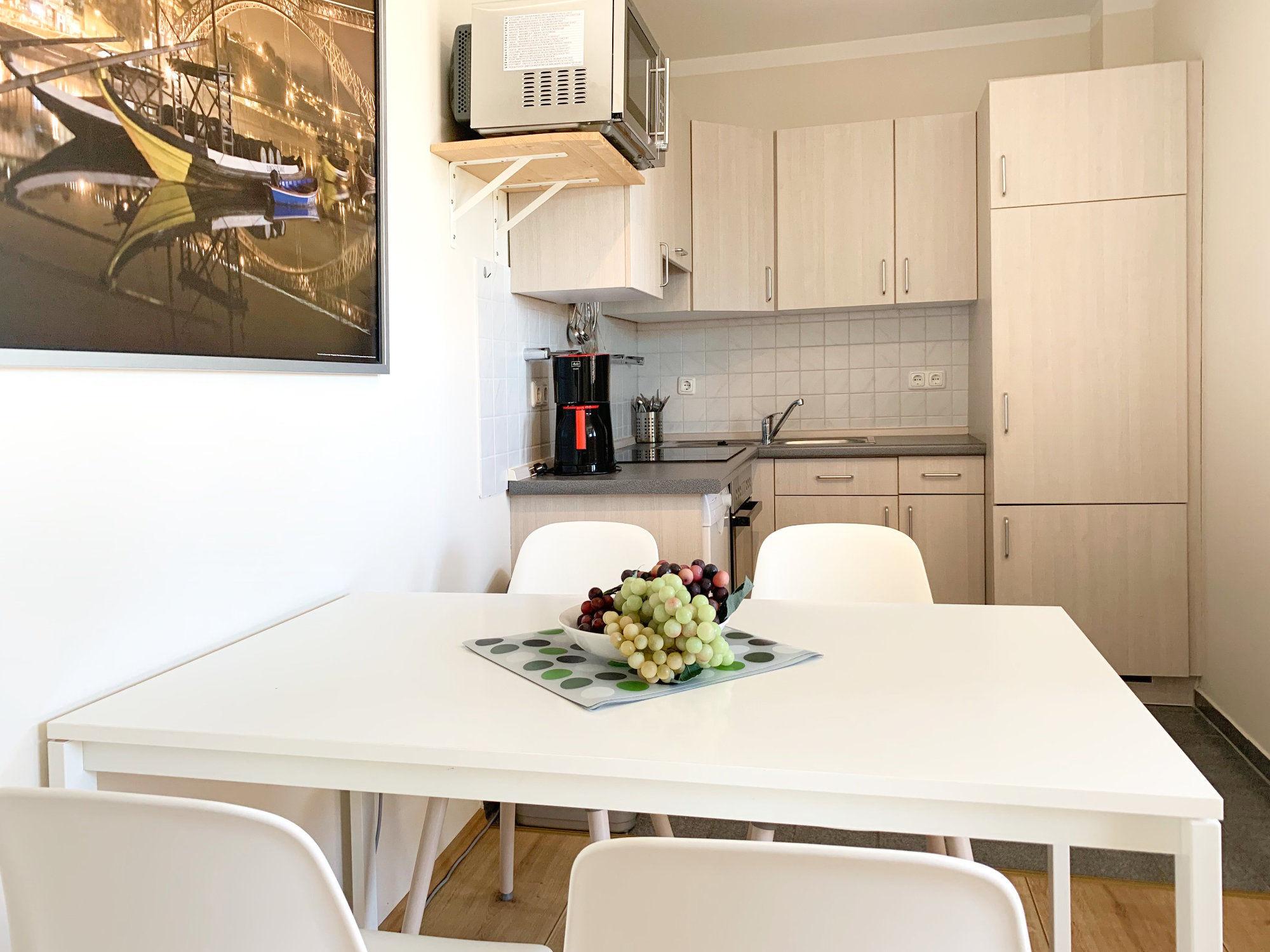 Esstisch mit 4 Stühlen, dahinter Bild von der Küche