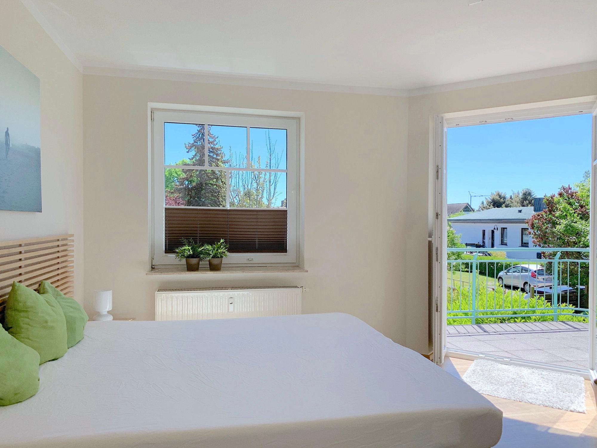 Schlafzimmer mit Doppelbett, große Fenster