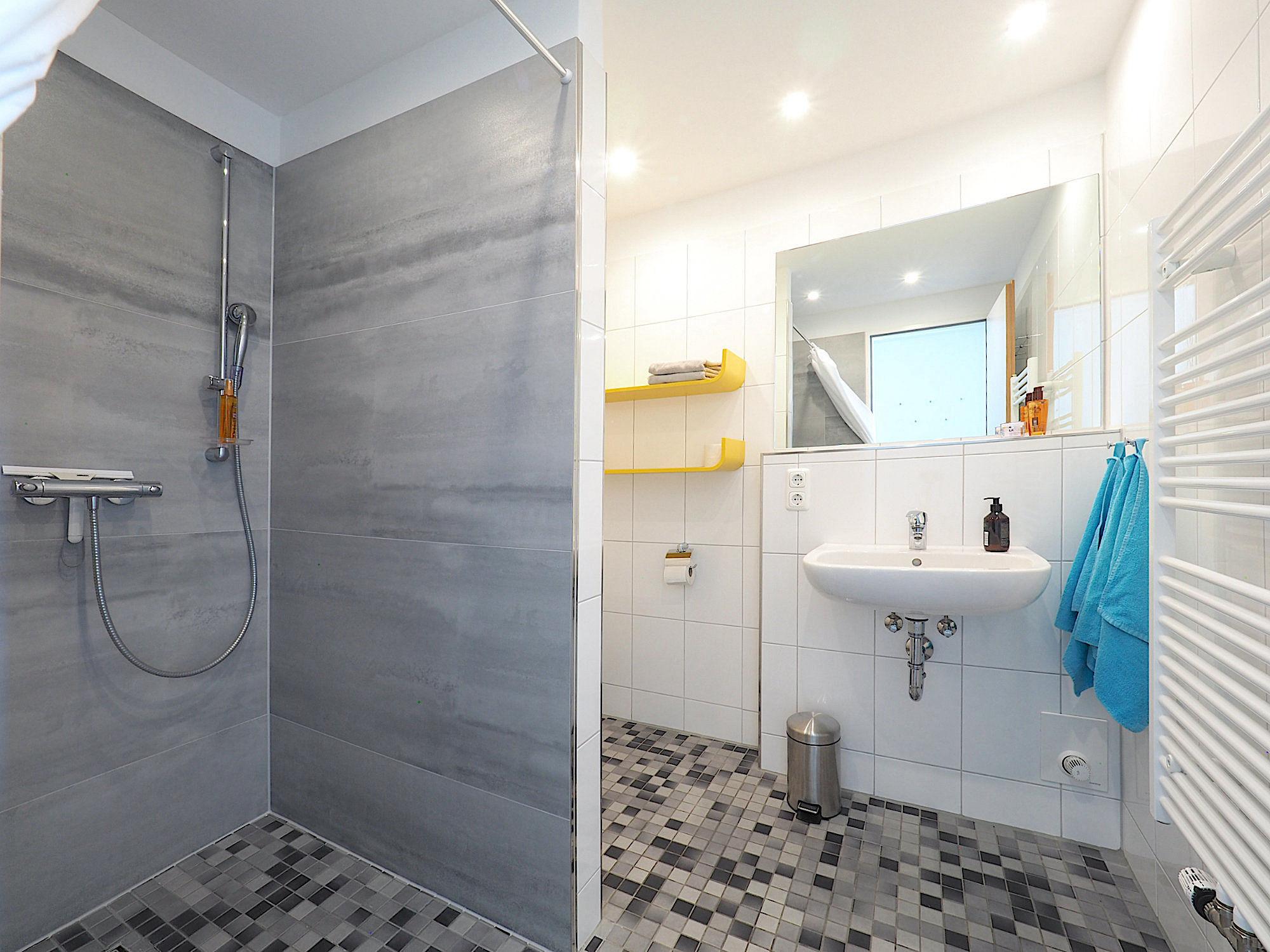 Duschbad mit bodentiefer Dusche, rechts davon ein Waschbecken und eine Handtuchheizung