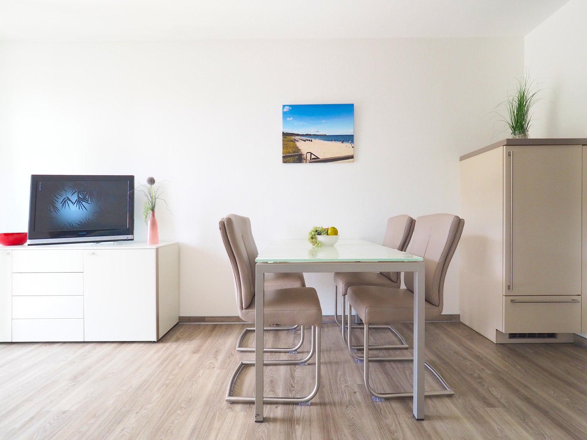Esstisch mit vier Stühlen, Sideboard mit Flatscreen-TV