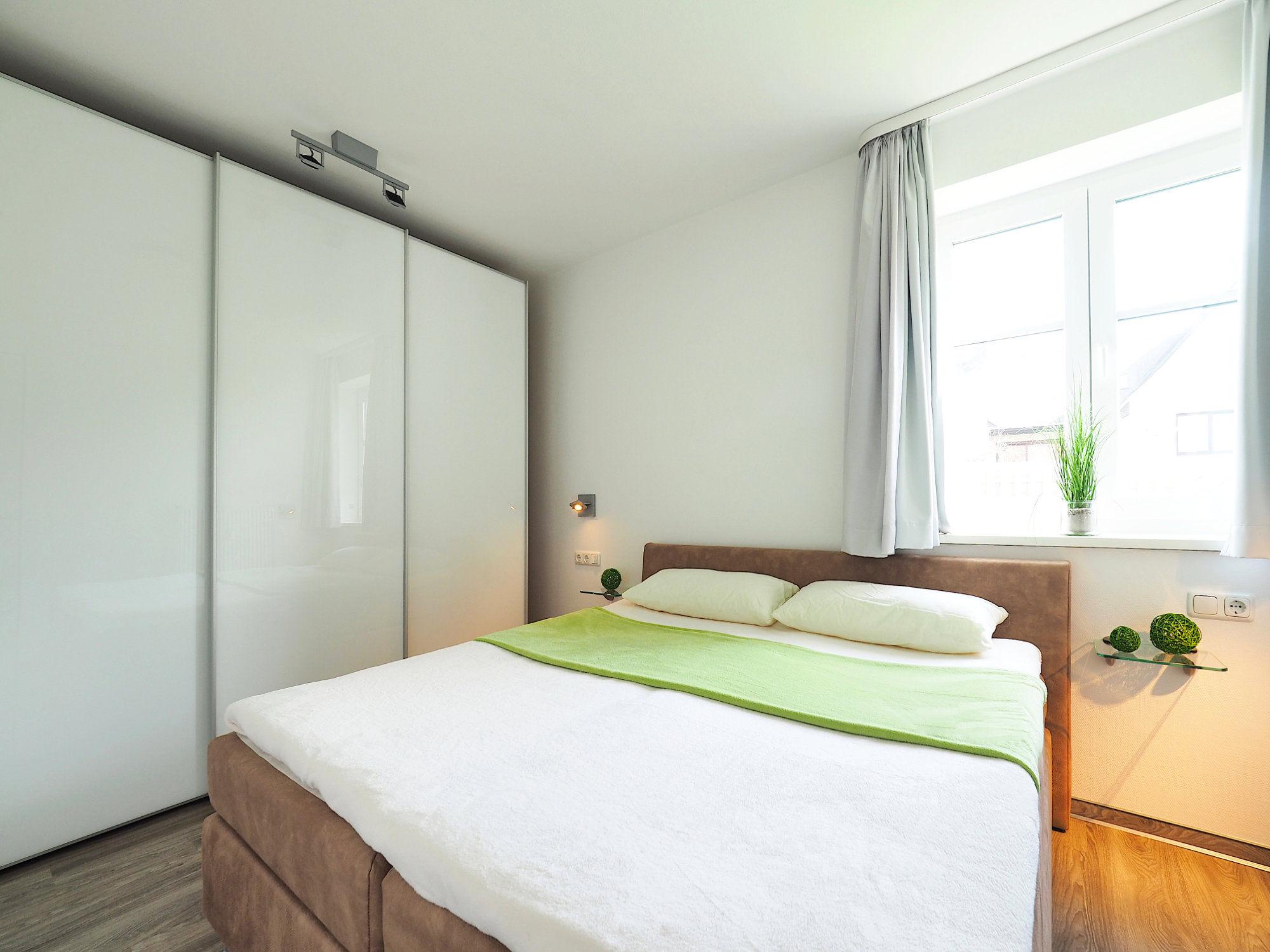 Schlafzimmer mit Doppelbett, Kleiderschrank und großem  Fenster