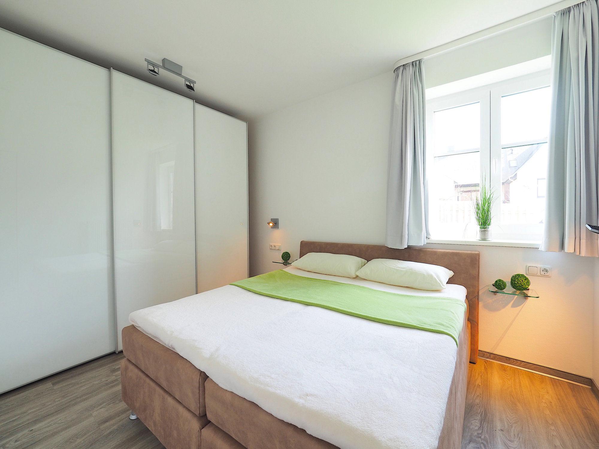 Schlafzimmer mit Doppelbett und großem Kleiderschrank und Fenster