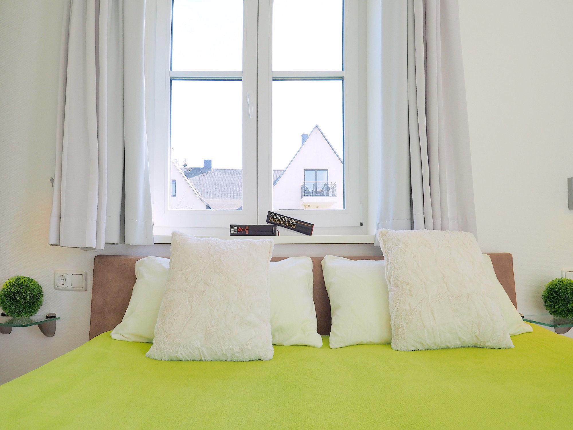 Zweites Schlafzimmer mit Doppelbett und großem Fenster