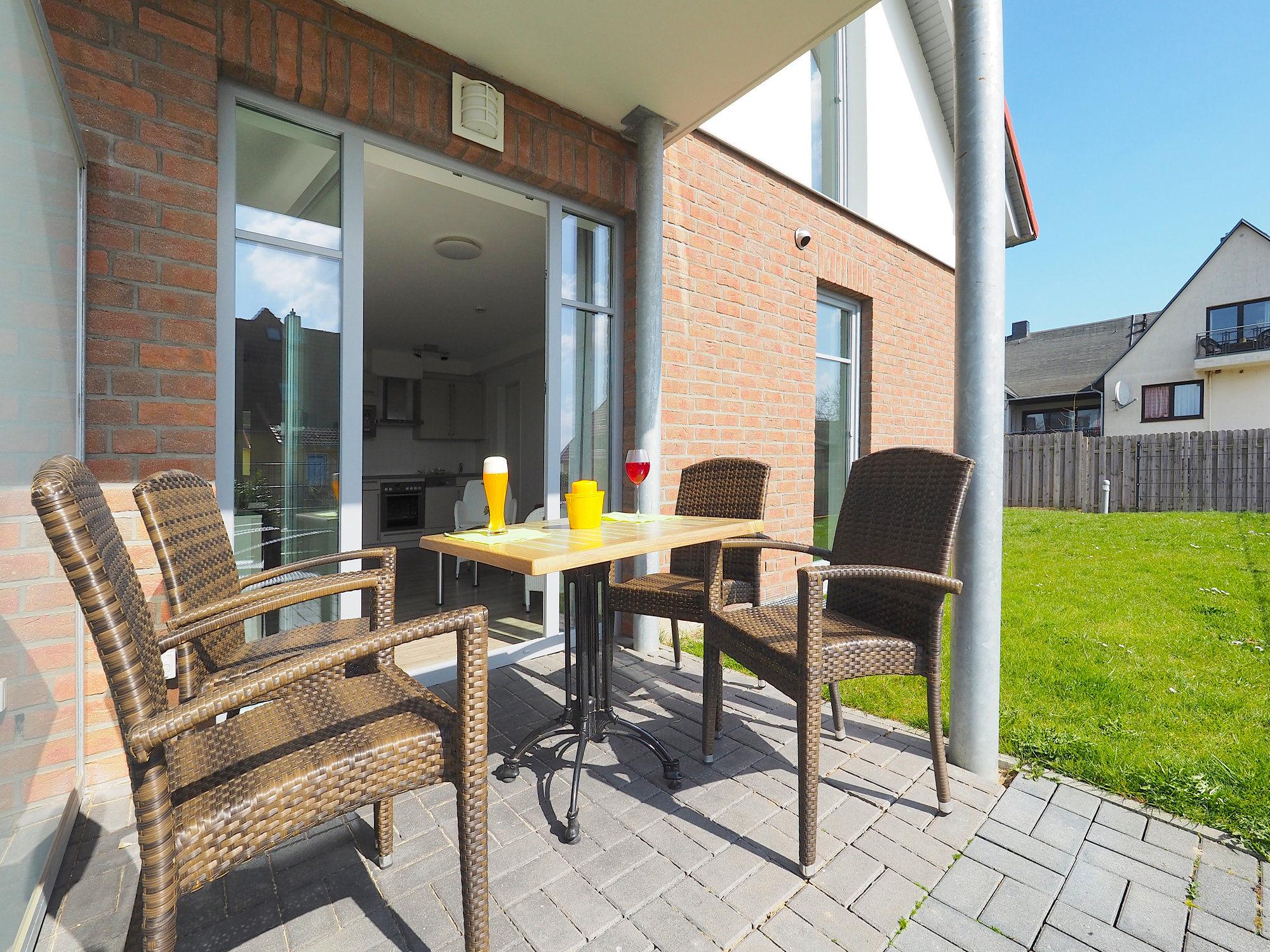 sonnige Terrasse mit Tisch und 4 Stühlen