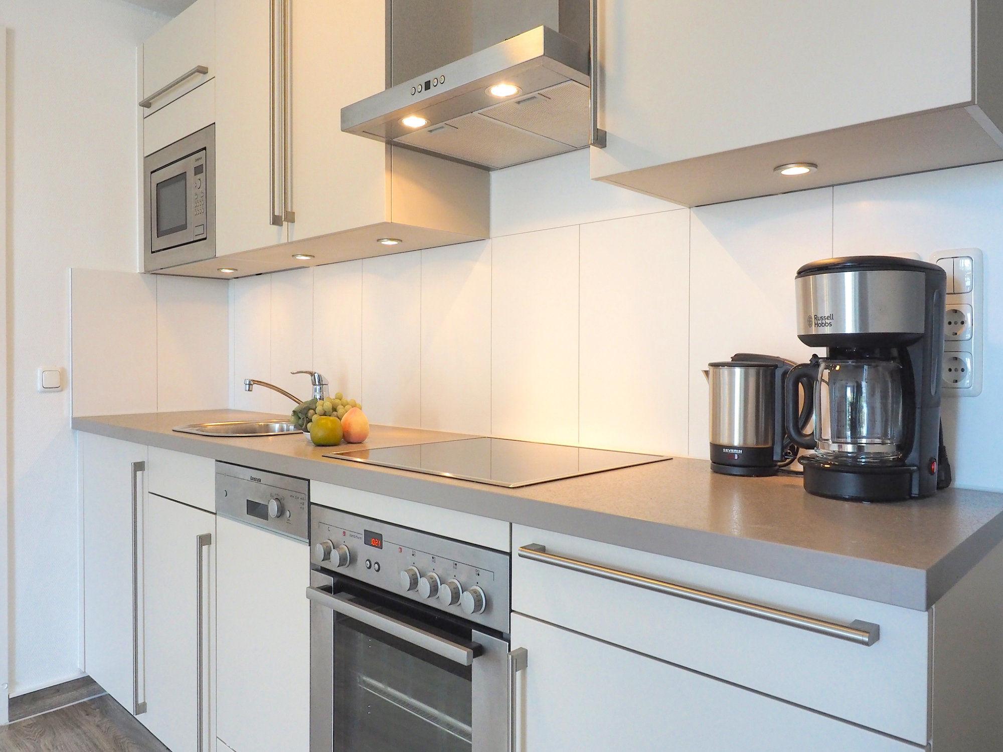 moderne Küchenzeile mit Backofen und Kaffeemaschine