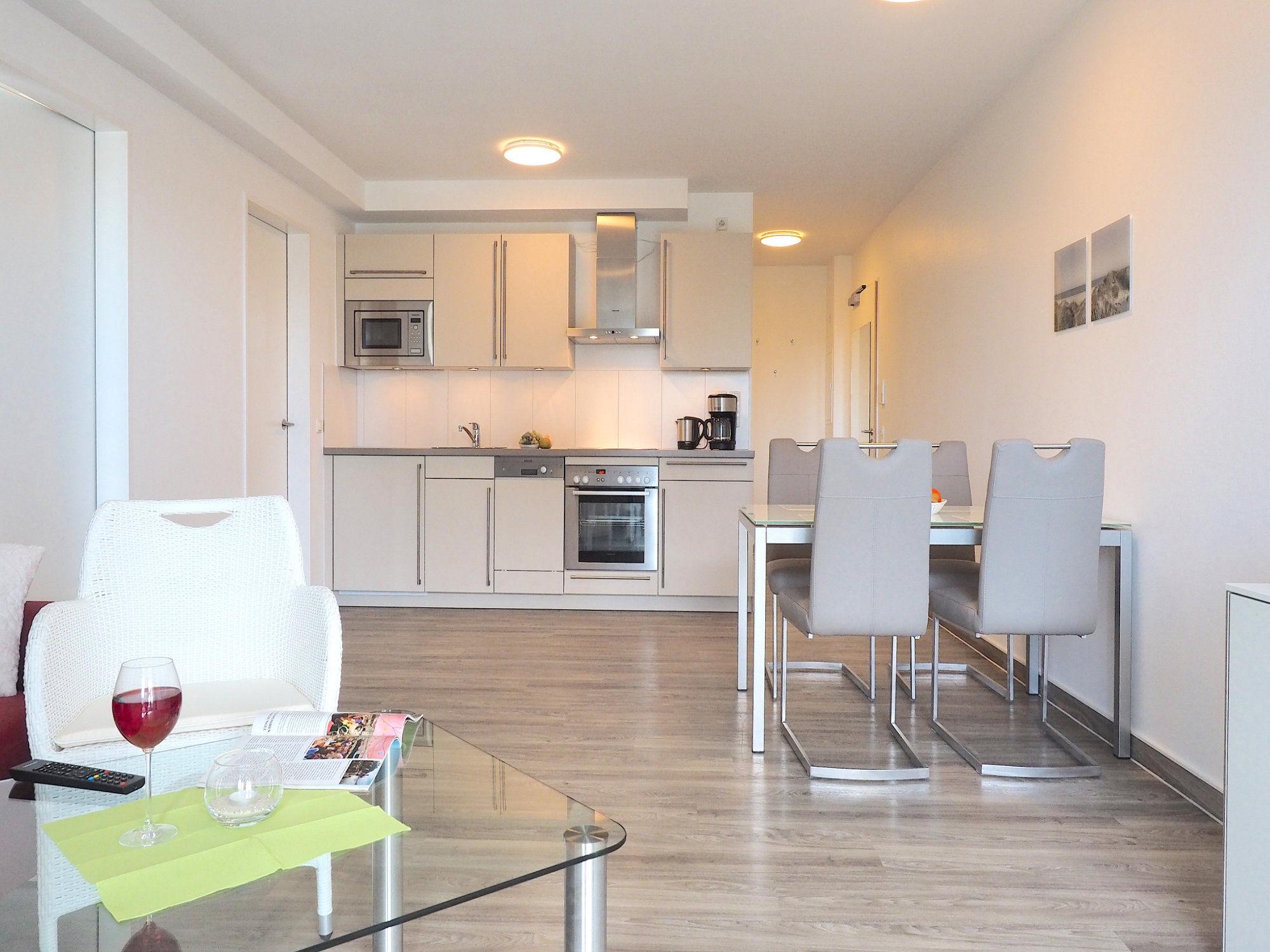 Im Vordergrund Glastisch mit Korbsessel, im Hintergrund rechts Tisch mit 4 Stühlen, dahinter Küchenzeile