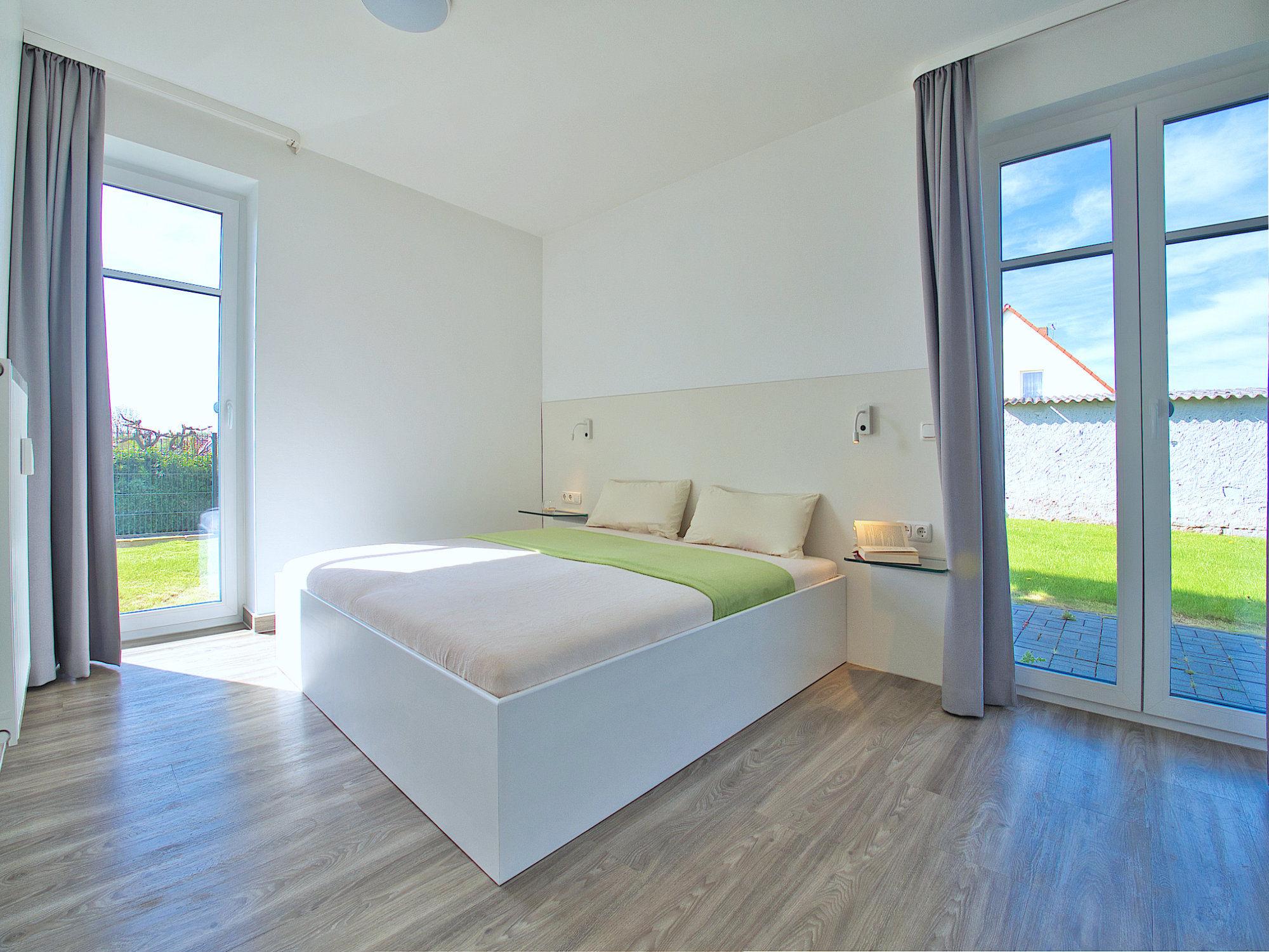Schlafzimmer mit Doppelbett und 2 bodentiefen Fenstern