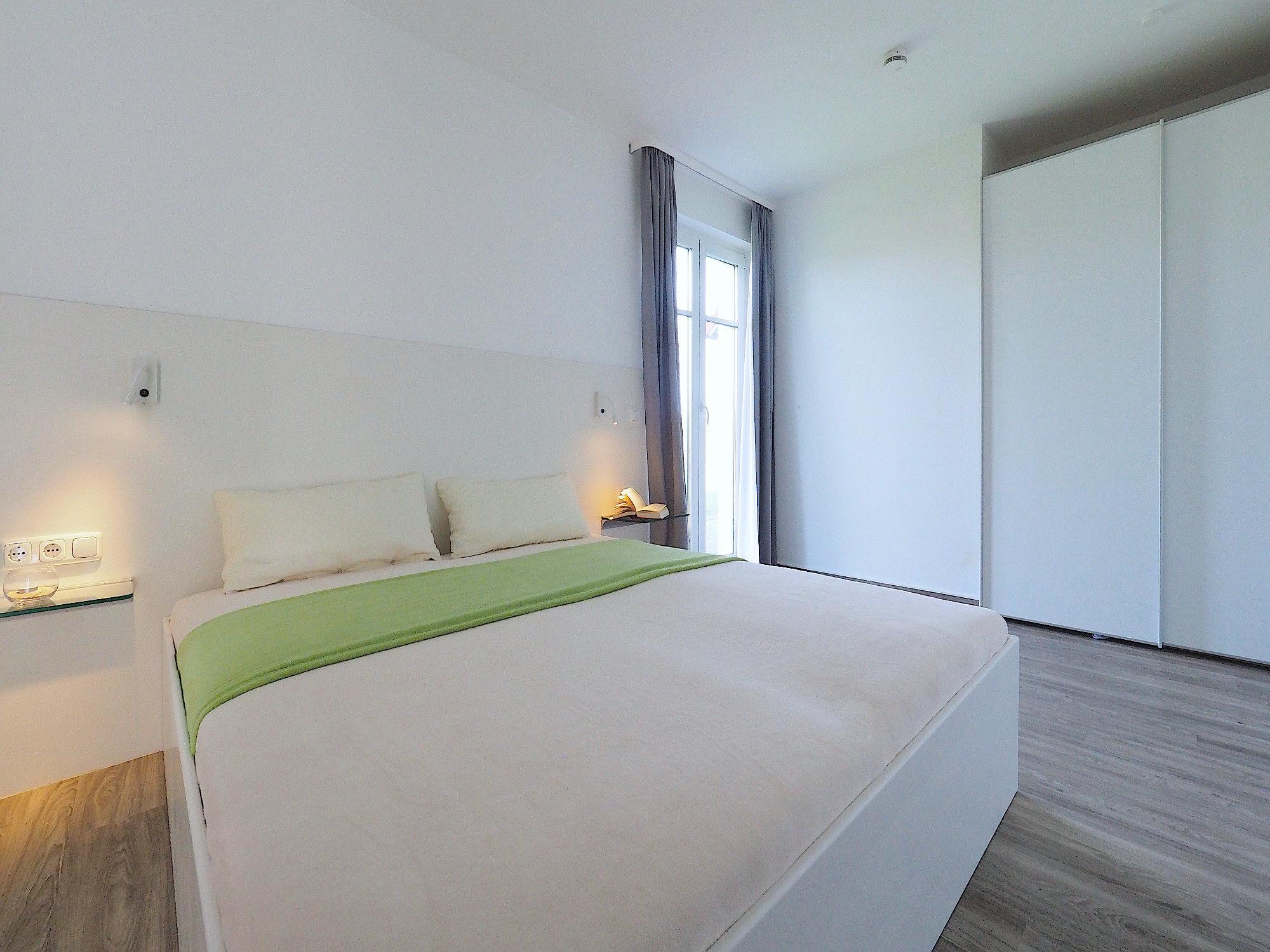 Schlafzimmer mit Doppelbett und Kleiderschrank und bodentiefem Fenster