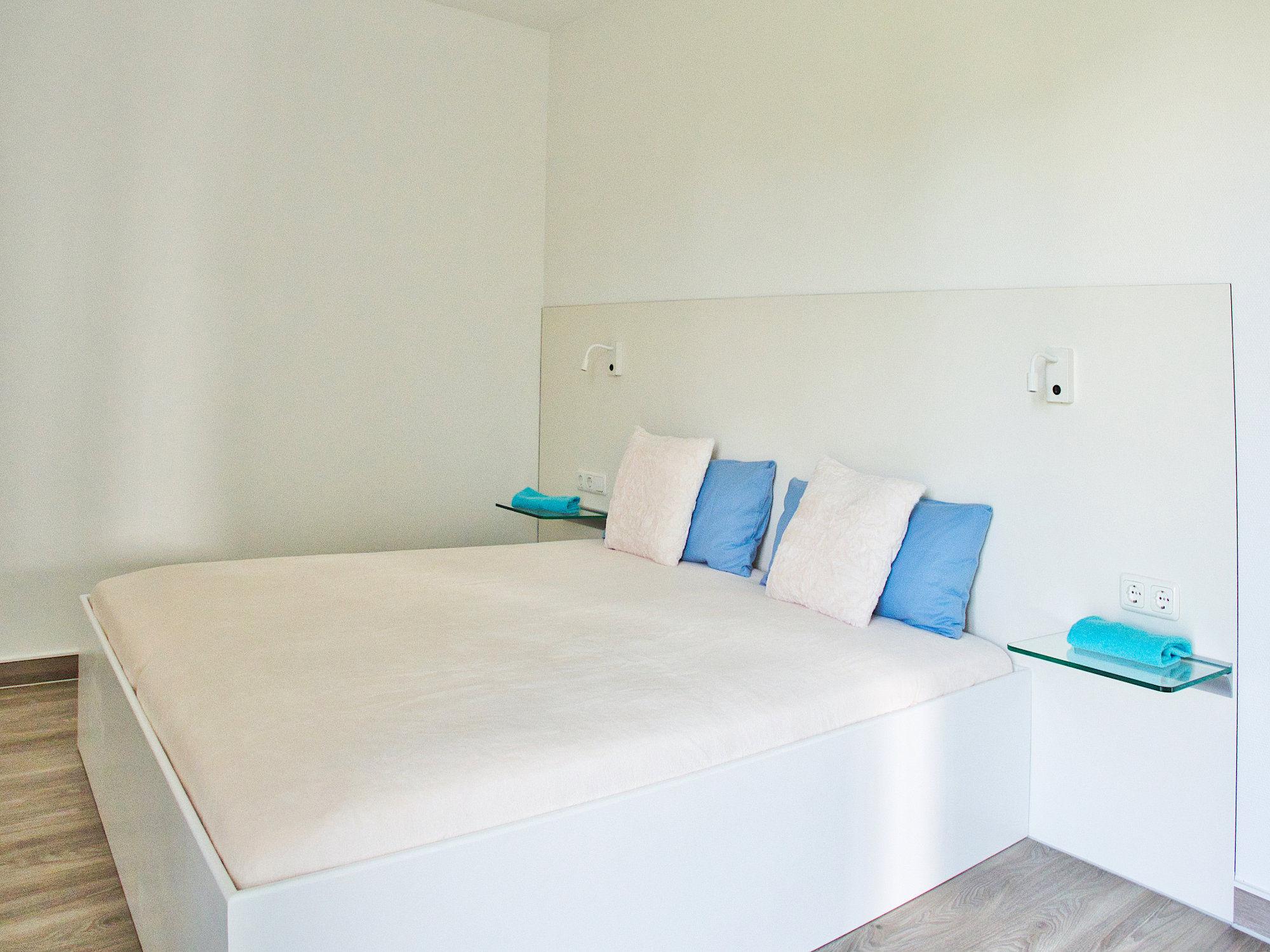 Zweites Schlafzimmer mit Doppelbett und Glaskonsolen