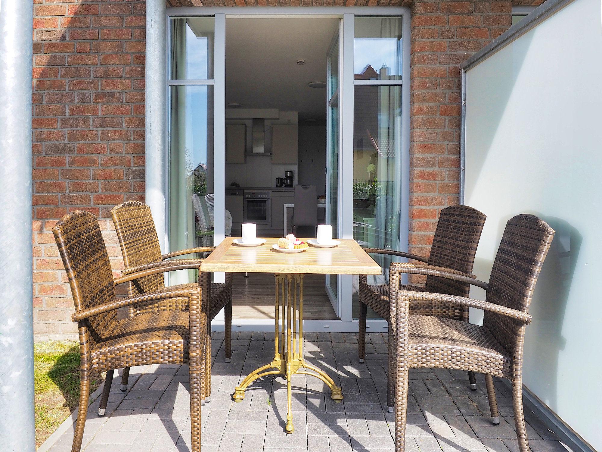sonnige Terrasse mit Tisch und vier Stühlen