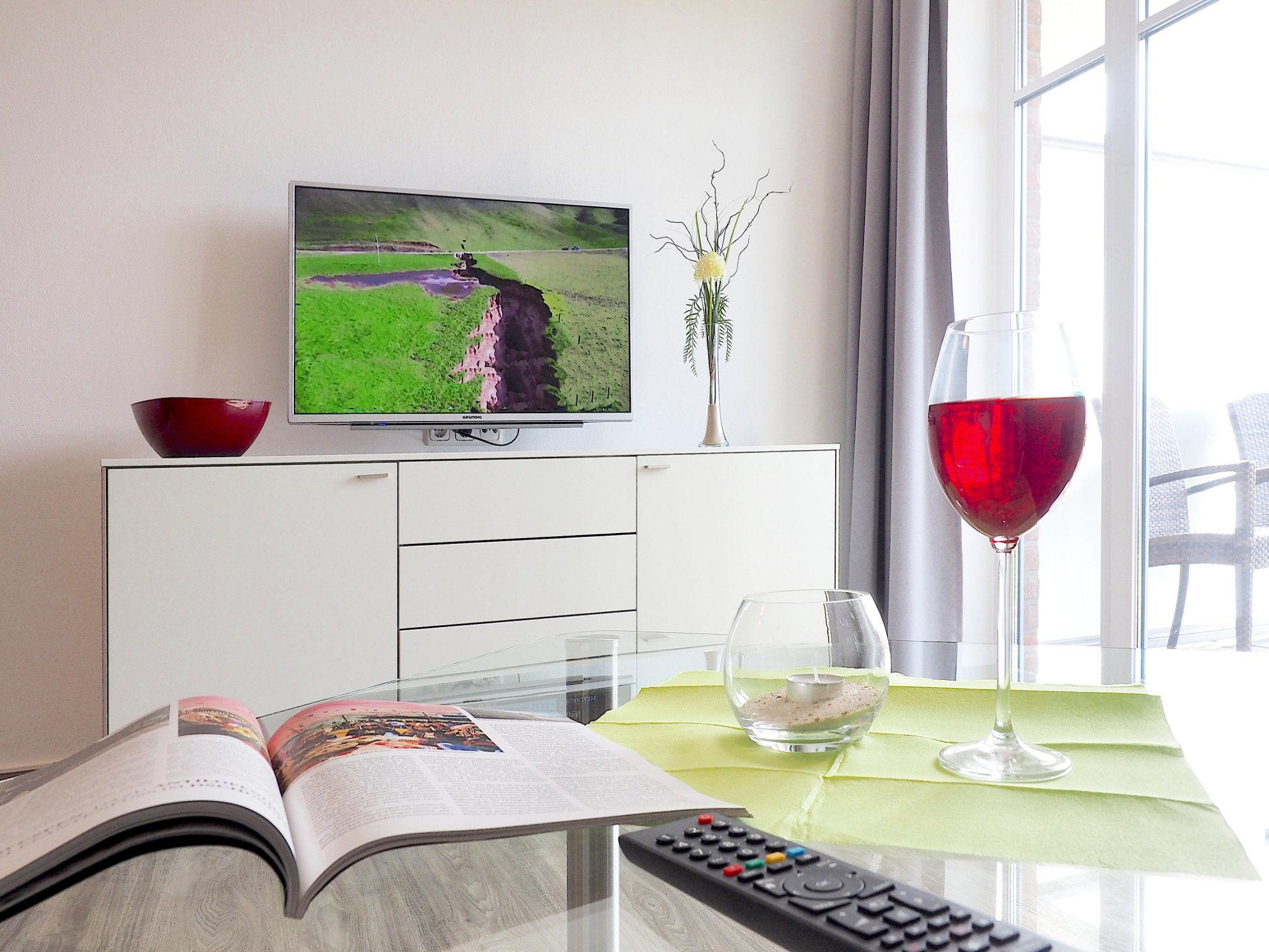 Wohnzimmer Sideboard mit Flatscreen-TV, im Vordergrund Glastisch