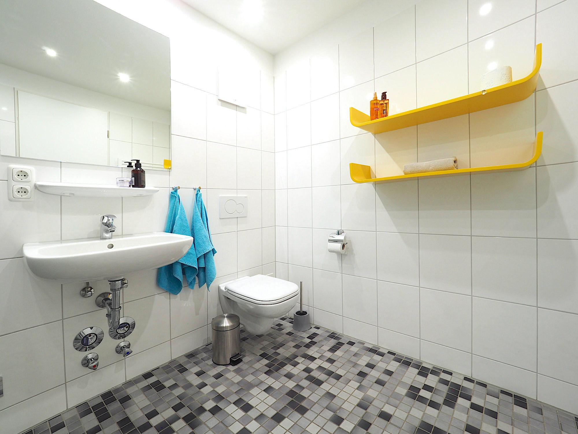 Duschbad mit Waschbecken, WC und zwei Regalen