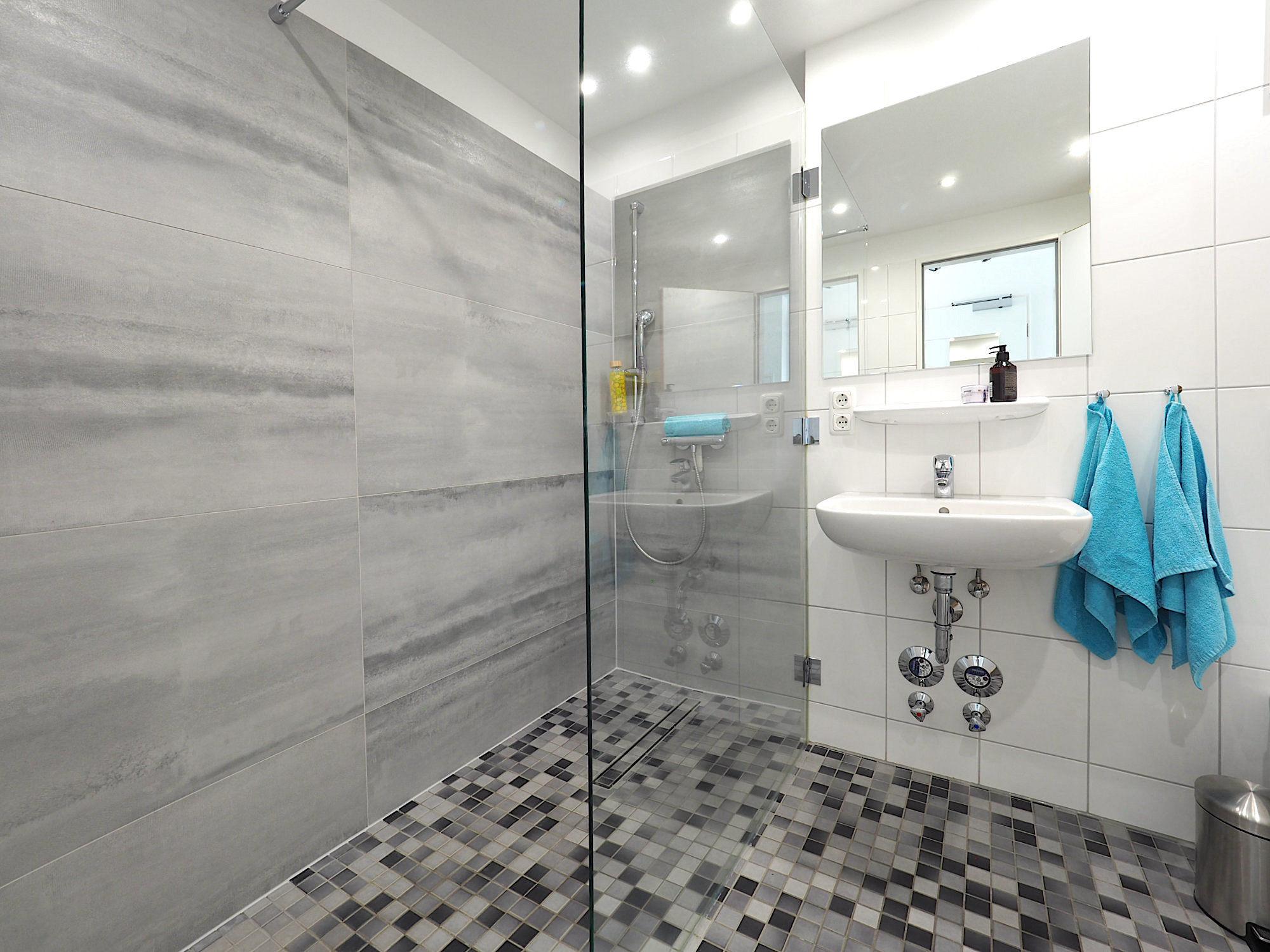 Duschbad mit bodentiefer Dusche und Waschbecken