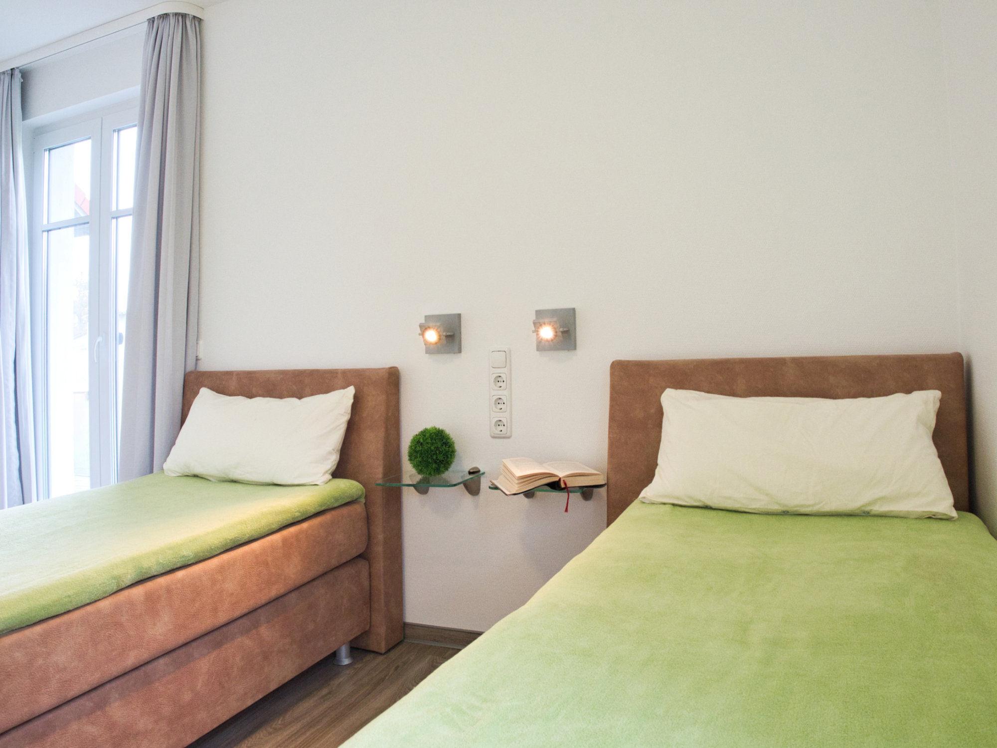 Schlafzimmer mit zwei Einzelbetten und einem bodentiefen Fenster
