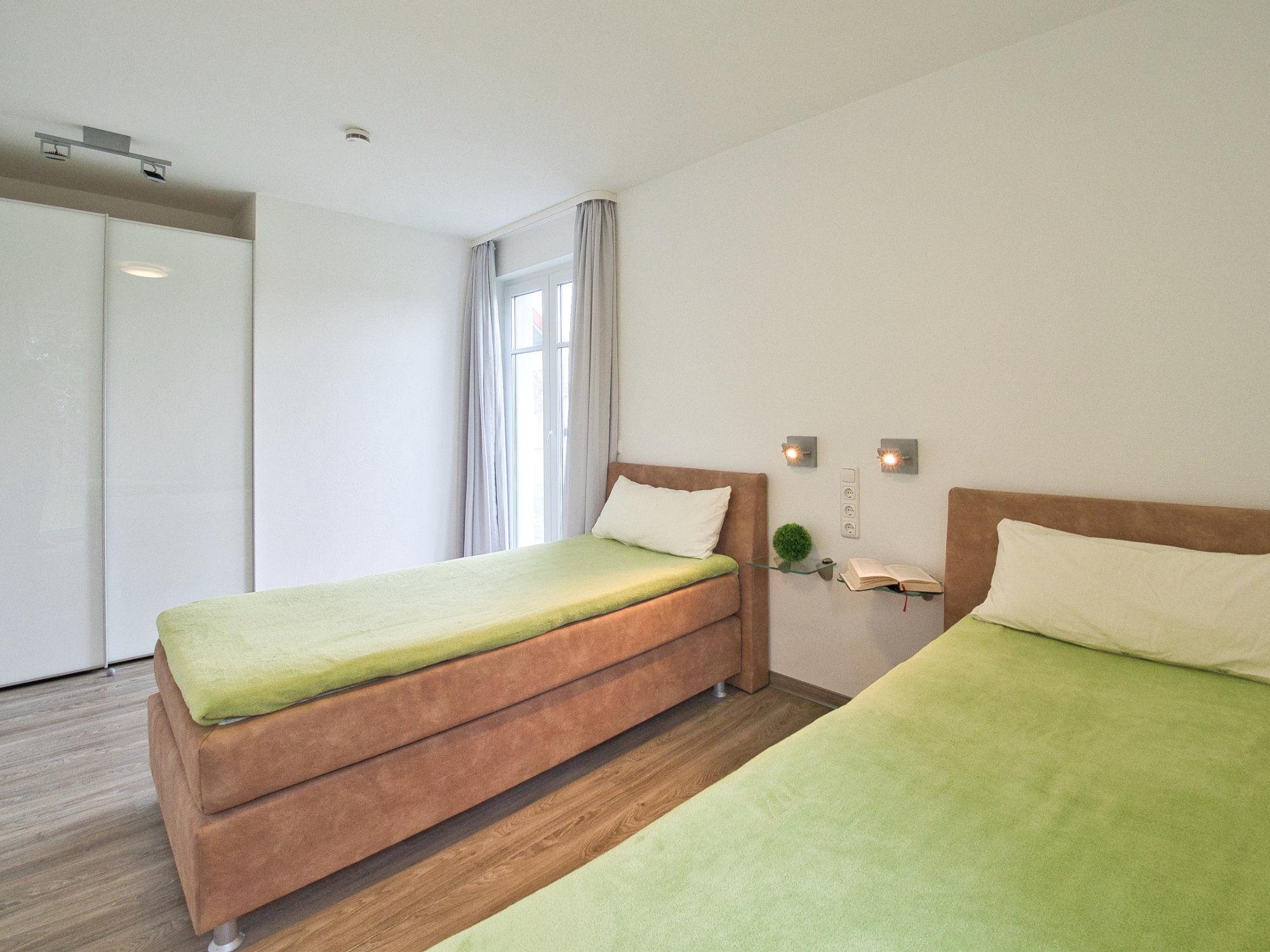 Schlafzimmer mit zwei Einzelbetten, großem Kleiderschrank und einem bodentiefen Fenster