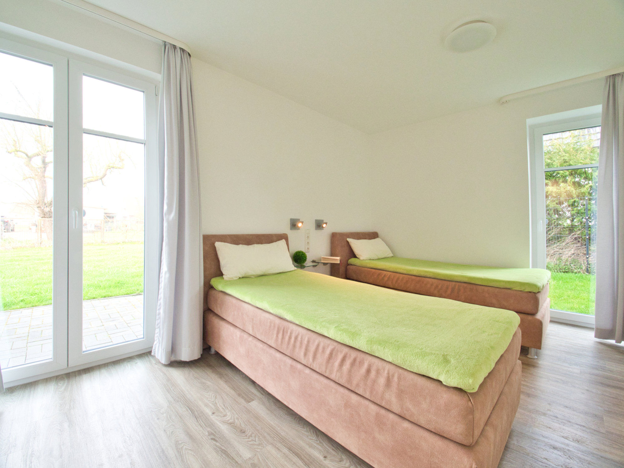 Schlafzimmer mit zwei Einzelbetten und 2 bodentiefen Fenstern